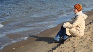Woman sits on sandy beach — Stock Video