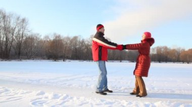 Couple having joined hands spins in snowfield — Stock Video