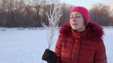 Portrait of woman blows to branchlet covered with hoarfrost — Stock Video