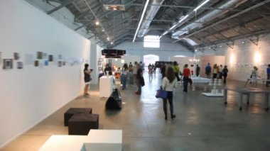 Walks and stands in exhibition hall — Vídeo de stock