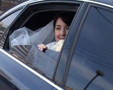 Bruid in trouwjurk zit in de auto en golven van haar hand — Stockvideo