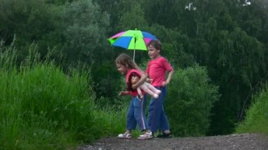 Menino e uma menina brincando com guarda-chuva no parque — Vídeo Stock