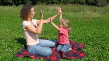 Mother with daugher plays pat-a-cake sits outdoor in field — Stock Video
