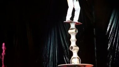 Acrobat trys to keep balance while standing on tower of cylinders in circus — Stock Video