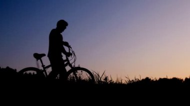 Man walking with bicycle against sunset sky — Stock Video