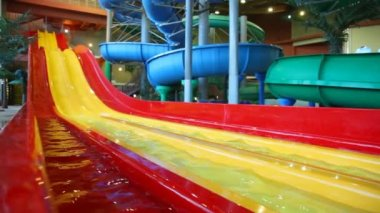 Large yellow plastic slide is filled a water in a large indoor waterpark — Stock Video