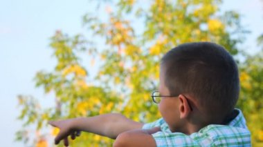 Portrait of bespectacled boy jerkes his finger forward in park — Stock Video