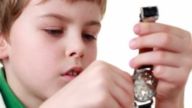 Boy starts a wristlet watch on white — Stock Video