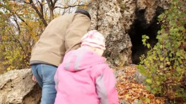 Daddy with daughter come into rocky cave — Stock Video