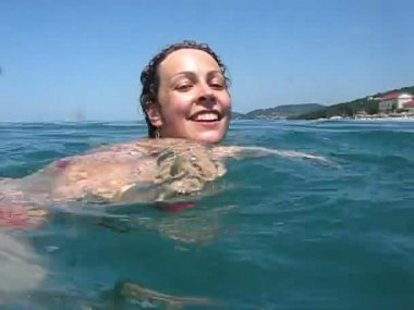 Woman in swimming suit swims in sea — Stock Video