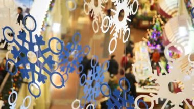 Close up paper snowflakes on cords, against shopping centre pavilions — Stock Video