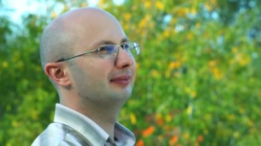 Portrait of smiling bald-headed bespectacled man stands against trees in park — Stock Video