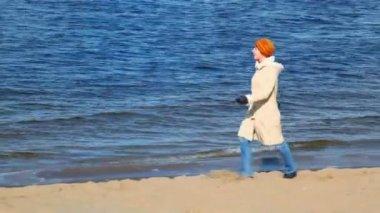 Woman walking along sandy bank — Stock Video