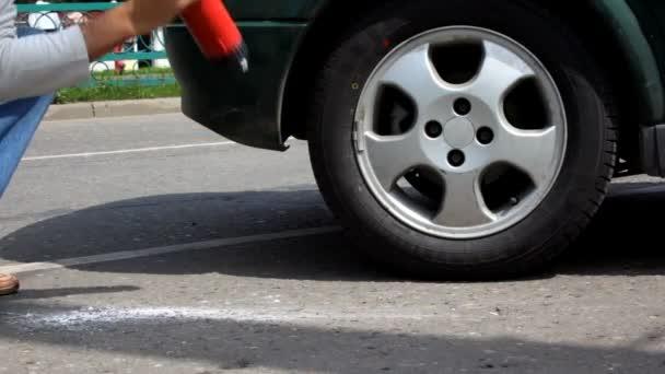 Homme bat moussant extincteur sur asphalte — Vidéo