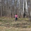 Cute little girl runs to camera in spring forest — Stock Video