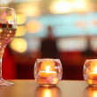 Stock Video: Candles putted inside glass and goblet filled with wine stand on table