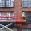 Workers standing on crane washing glass windows in brick house — Stock Video