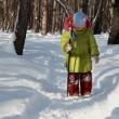 Little girl walks with ski stick in winter wood — Stock Video #27512627