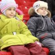 Girl and boy sit on armchairs, attentively watch hockey match — Stock Video #27513045