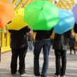 Young men spin colorful umbrellas back to camerthen jump up — Stock Video #27513247