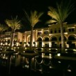 Fountains and palms in front of office Paris Gallery Group at night in Dubai, UAE. — Stock Video