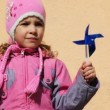 Stock Video: Girl holding toy windmill left hand
