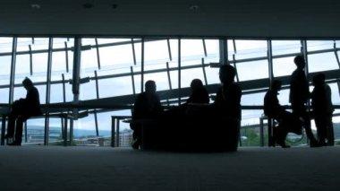силуэты напротив окон в аэропорту. — Стоковое видео