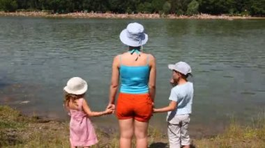 Family on river bank in summer day. — Vídeo de Stock