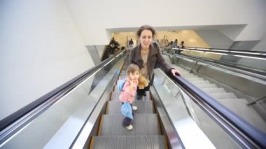 Mother and daughter moving up on escalator — Stock Video