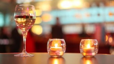 Candles putted inside glass and goblet filled with wine stand on table — Stock Video