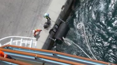 Workers unbends mooring line of cruise ship from moorage — Stock Video