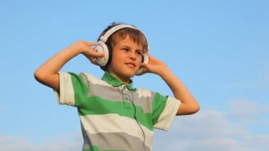 Boy with closed eyes listen to music through headphones and dancing — Stock Video