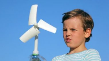 Boy holding toy wind-driven generator in his hands — Stock Video