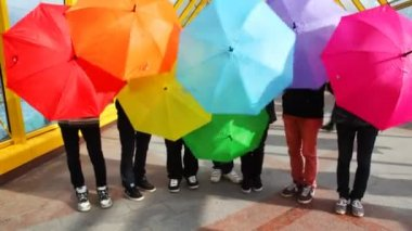 Men spin colorful umbrellas and make them lower down — Stock Video