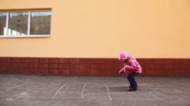 Boy and girl playing hopscotch jumping — Stock Video