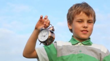 Boy holding in his hand ringing alarm clock — Stockvideo