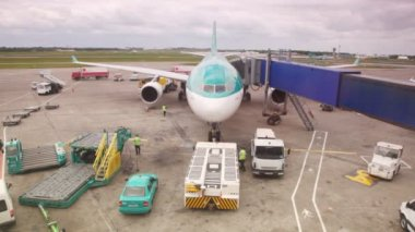 Airplane standing at airstrip is serviced by airport workers — Stock Video