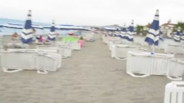 Camera quickly moves on a beach between chaise lounges and umbrellas. — Stock Video