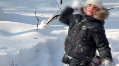 Boy walks and plays snowballs in winter wood — Stock Video