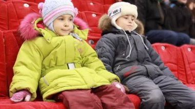 Girl and boy sit on armchairs, attentively watch hockey match — Stock Video