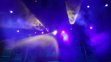 Moving disco searchlights in smoke on stage of nightclub — Stock Video