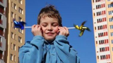 Boy put his cheek two toys windmill — Stock Video