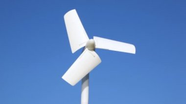 Tiny wind driven generator beginning to turn against sky — Stock Video