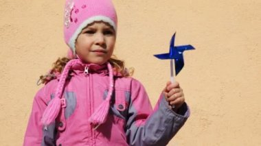 Girl holding toy windmill left hand — Stock Video