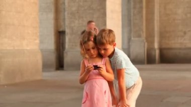 Children are on the square and watching video on smartphone. — Stock Video