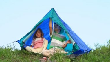 Boy and his kid sister sits under tent out of town — Stock Video