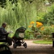 Calm old man reading newspaper sitting on bench near baby carriage — Stock Video