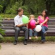 Family play game with balloons sitting on bench in park — Stock Video #27545281