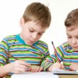 Girl and boy with a chocolate-smeared mouth draw pictures in notebooks — Stock Video