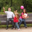 Stock Video: Family play game with balloons sitting on bench in park